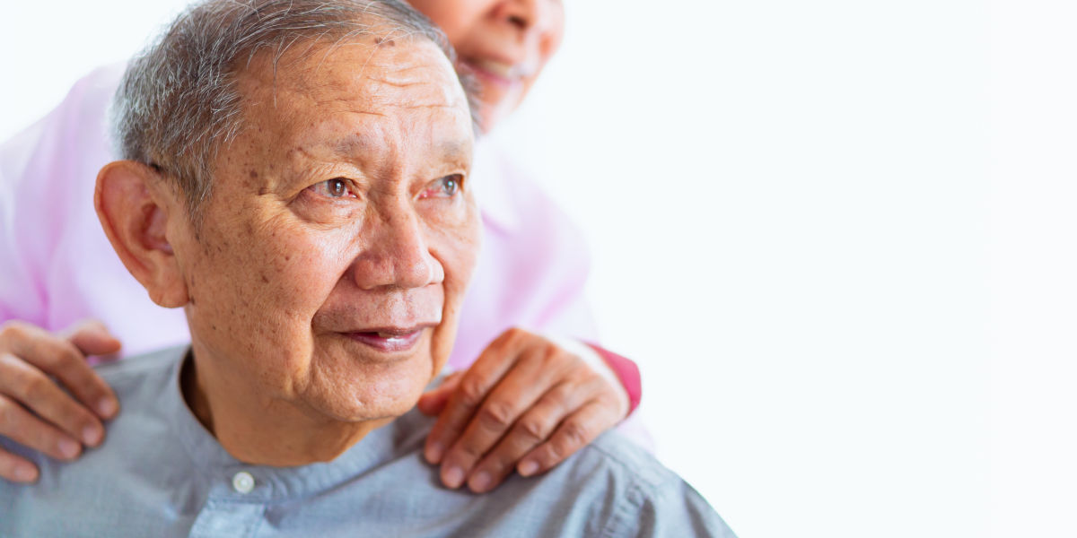 Asian woman with hands on shoulders of seated Asian man