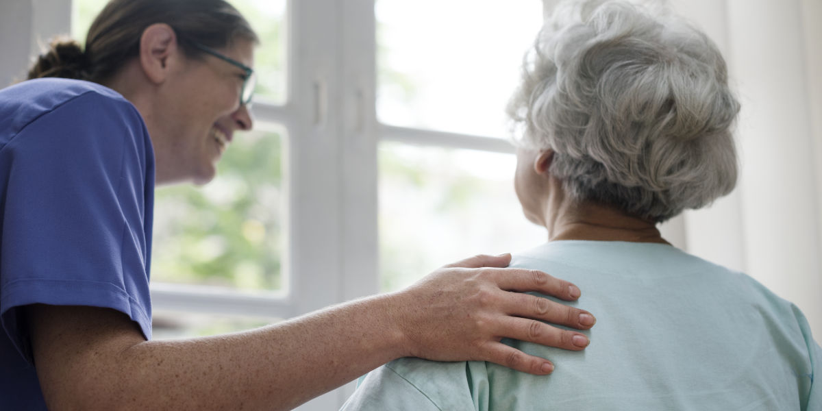 Care worker with hand on older woman's shoulder
